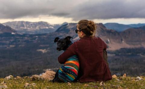 woman sitting near dog on cliff overlooking mountains